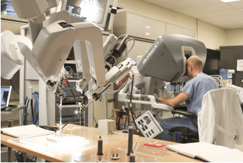 Demonstration of our set-up in the ISIS simulation center with the da Vinci. Tasks are affixed to acrylic plates so that the orientation of the robot remains constant between modules. (Resident: Daniel Avery, Urology PGY-4)