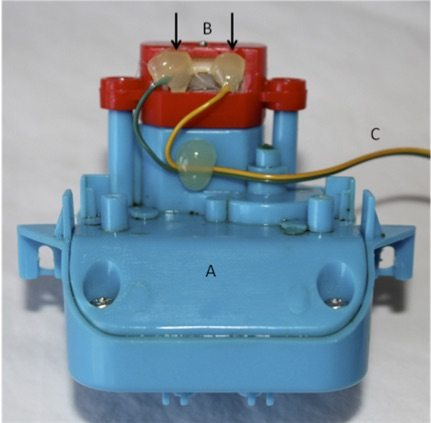 Motor isolated from the vibratory toy. The eccentric gear transition is housed in a plastic case providing vibration (A). The leads from the motor (B) were soldered to 2 wires (C) that connected to the receiver