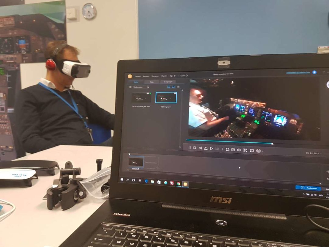 Participants in the program from KLM utilize VR goggles to simulate a scenario from the training. The instructor looks on, using the laptop to display what the pilot wearing the goggles is seeing.